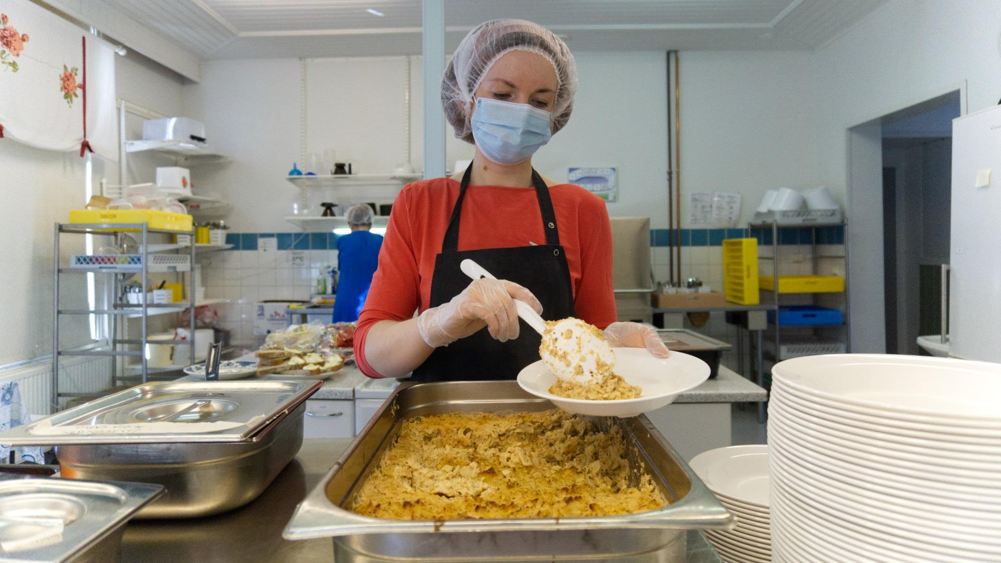 Kouluemäntä panee ruokaa lautaselle, kuva