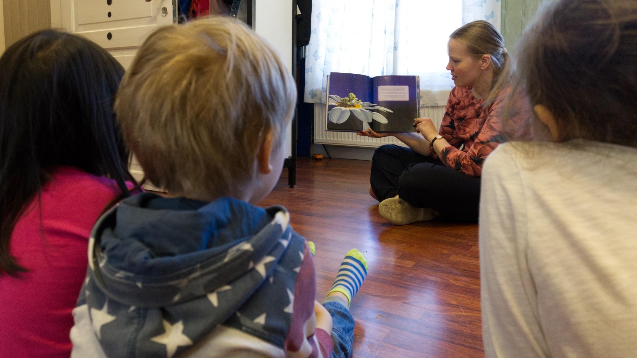 Opettaja lukee kirjaa lapsille lattialla, kuva