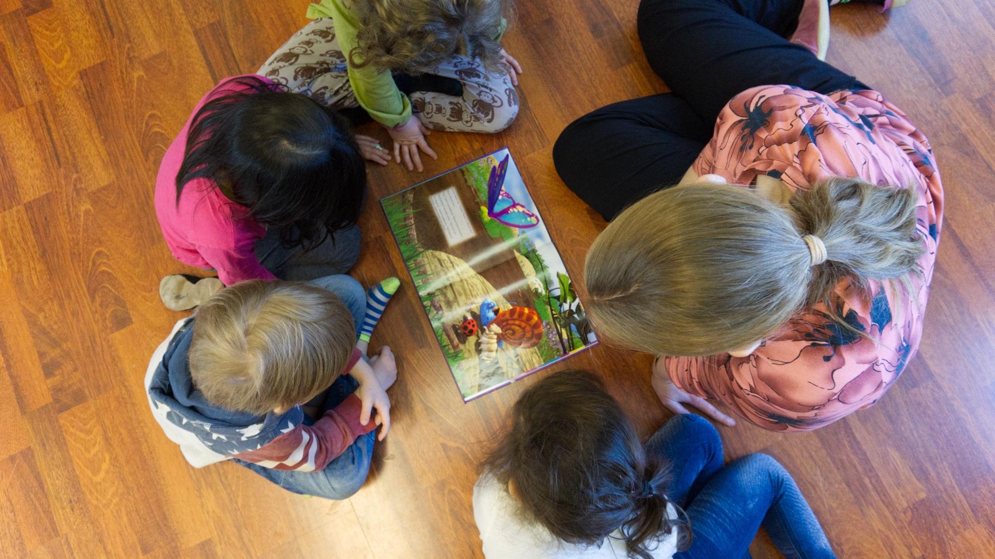 Opettaja ja lapset lattialla ympyrässä lukemassa kirjaa, kuva